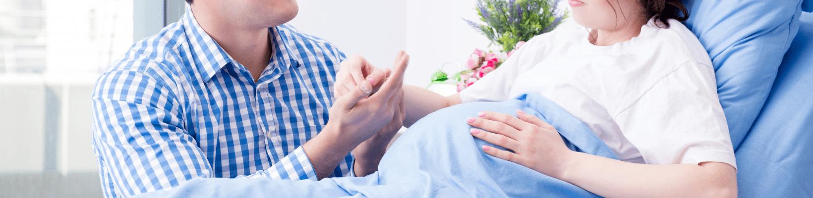 mąż odwiedza ciężarną żonę w szpitalu